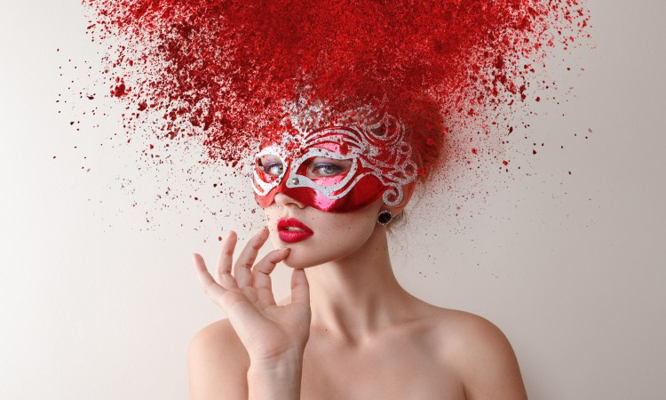 48540570 - young fashion model with carnival mask and exploding powder hairstyle